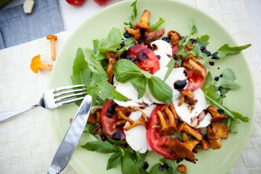 На тарелку с моцареллой и помидорами выложите рукколу, горячие лисички и базилик, сбрызните оливковым маслом и бальзамическим уксусом. Наш салат с моцареллой и руколой готов. Приятного аппетита!
