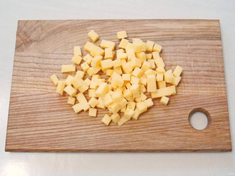 Сыр порежьте мелким кубиком.