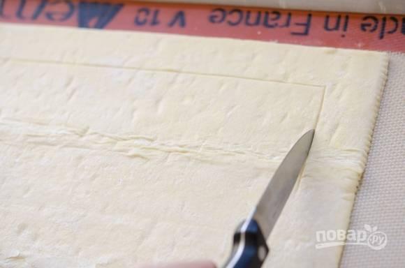 1. Размороженое слоенное тесто поместите на бумагу для выпечки, обратной стороной ножа наметьте линию по контуру теста не прорезая его.