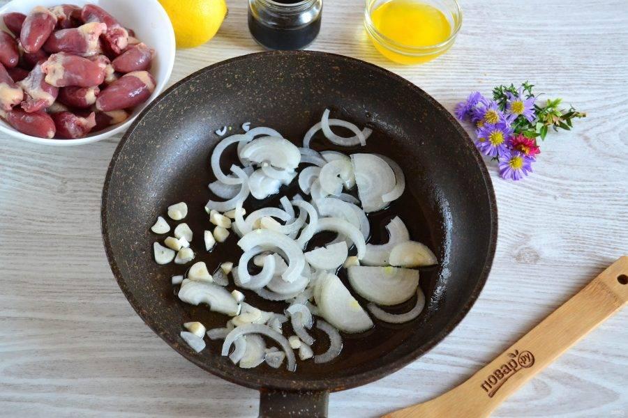 В сковороде разогрейте растительное масло, выложите лук и чеснок, обжарьте на среднем огне.