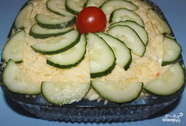 6.Яйца смазываем майонезом, натираем сыр и укладываем верхним слоем. Украшаем порезанным огурцом и помидором черри. Настаиваем салат 30 минут и подаем к столу.