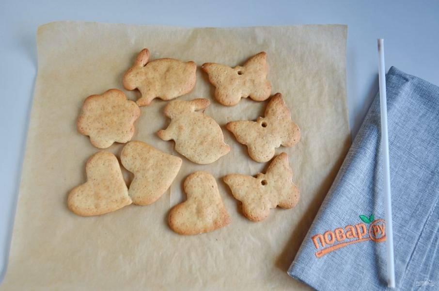 Готовое печенье, пока горячее, очень мягкое, поэтому трубочкой можно сделать отверстия для ниточек, чтобы повесить их потом на ёлочку.