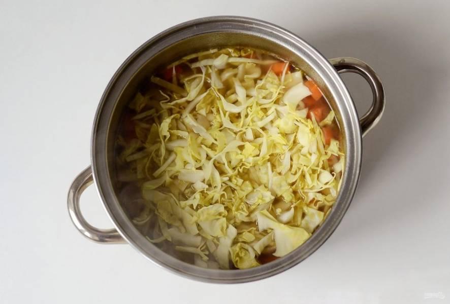 Порежьте капусту, добавьте в кастрюлю. Готовьте суп еще 5-7 минут.