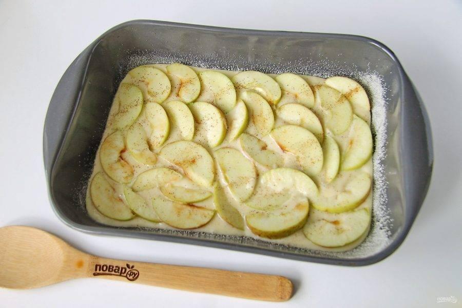 Форму для выпечки смажьте маслом, дно и бока присыпьте мукой или манкой. Если форма разъемная, то предварительно застелите ее пергаментом. Половину теста вылейте в форму и разровняйте его лопаткой. Поверх теста выложите равномерно половину нарезанных яблок и посыпьте их корицей.