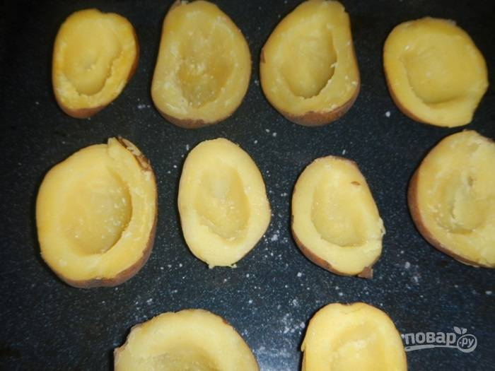 На противень выложите наполненные картофельные лодочки.