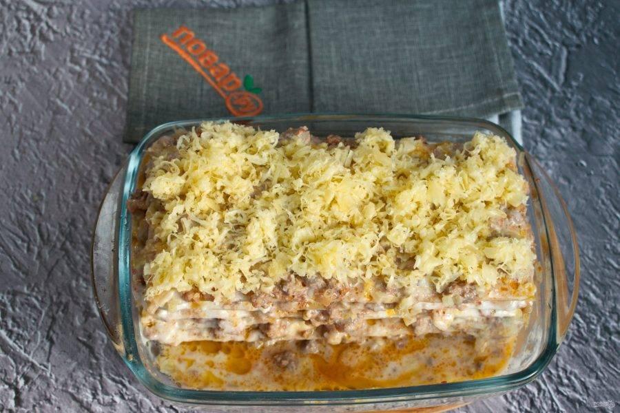 """Затем лист лазаньи, опять мясной соус, """"Бешамель"""" и тертый пармезан.  Чередуйте последующие слои в том же порядке. Обязательно смазывайте соусом углы листа лазаньи, чтобы при выпекании он не высох и не остался жестким.  Верх лазаньи посыпьте тертым сыром. Поставьте ее запекаться в разогретую духовку на 20-25 минут."""