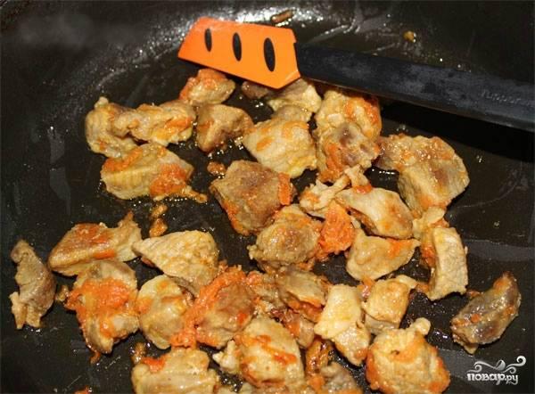 3. Мясо порежьте на небольшие по величине кусочки. Морковь помойте, очистите от шкурки и потрите на средней терке. В отдельную сковородку налейте немного растительного масла и выложите мясо с морковью, поставьте на средний огонь. Поджарьте мясо с морковью до полуготовности, примерно минут 10-15.