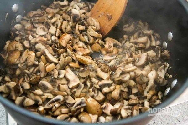 В большом сотейнике начните жарить грибы, порезанные дольками. Добавьте немного соли. Масло не нужно. Когда грибы станут выделять жидкость, добавьте измельченный лук.