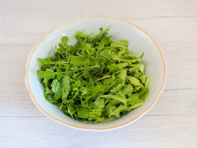 Рукколу и салатный лист вымойте, стряхните воду, выложите в просторный салатник.