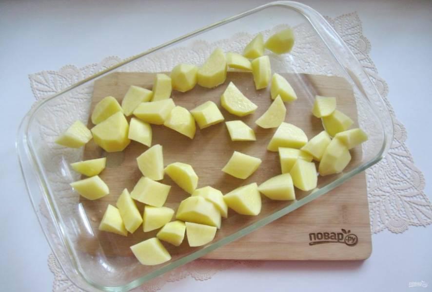 Картофель очистите, помойте и нарежьте, не очень мелко. Выложите в жаропрочную форму.