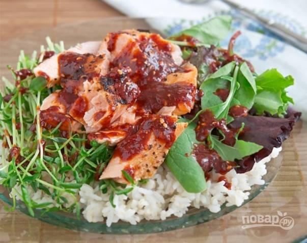 Сверху уложите рыбку. Соус налейте в соусник и поставьте рядом, или сразу полейте им рыбу и подавайте блюдо к столу.