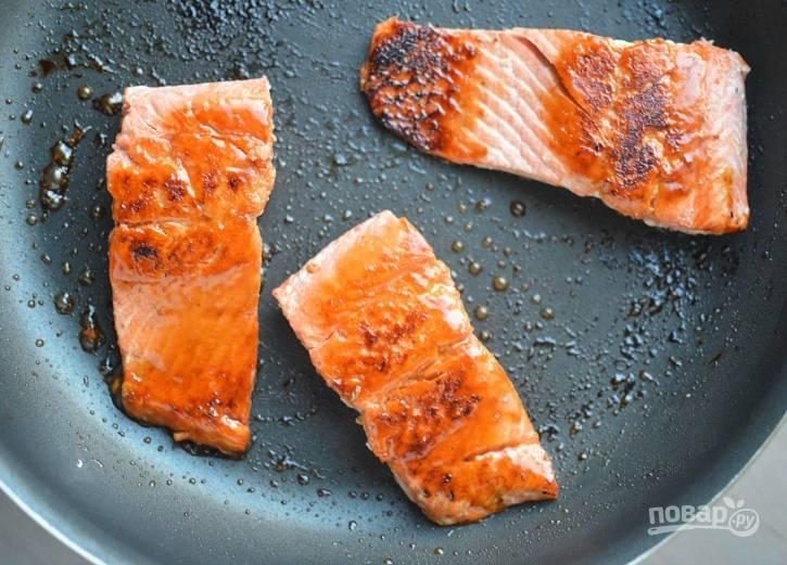 2. В это же время натрите солью и перцем рыбу. Вначале обжарьте её 3 минуты в масле, потом в сковороду добавьте мёд. Обжарьте лосося с другой стороны ещё 3 минуты.