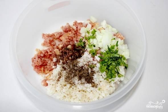 Теперь в миску с фаршем добавляем половину измельченного лука и зелени, рис, яйцо, а так же специи и пропущенный через пресс чеснок. Тщательно перемешиваем все ингредиенты и ставим фарш на пол часика в холодильник.