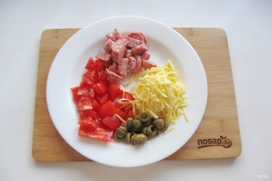 Нарежьте помидор, оливки, колбаски. Сыр натрите на терке.