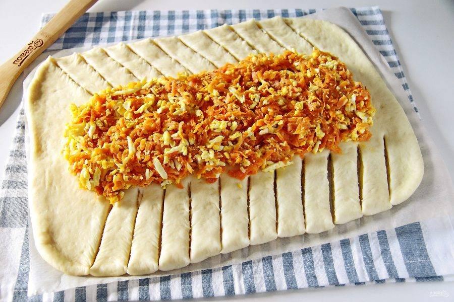 Раскатайте тесто в форме прямоугольника, толщиной примерно 4-5 мм. По центру выложите начинку. Боковые части теста нарежьте полосками как на фото.