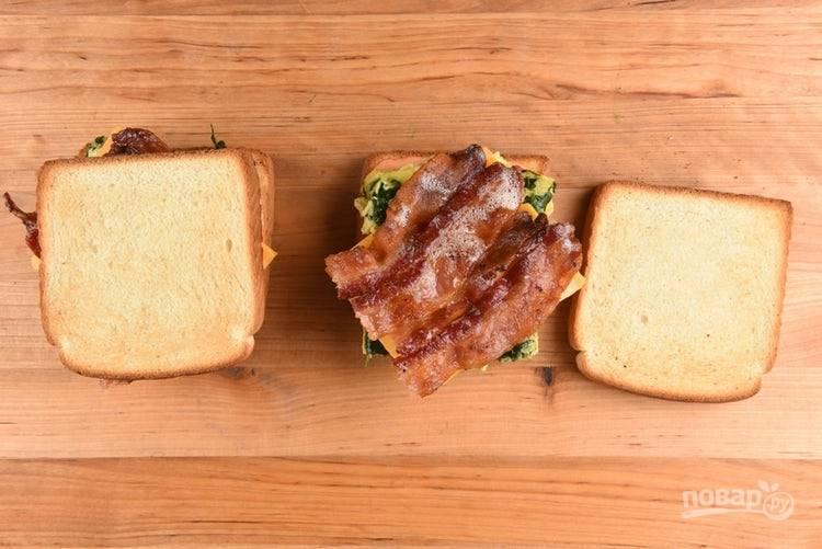 5. Хлеб приготовьте в тостере или на сковороде до хрустящей корочки. Затем на два кусочка распределите соус, далее яйцо, ломтик сыра и бекон.