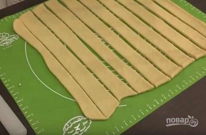8. Выложите тесто на стол, его немного нужно обмять. Разрежьте на 2 части, чтобы было удобнее с ним работать. Раскатайте каждую часть квадратом и нарежьте тонкими полосами (3-4 см. шириной).