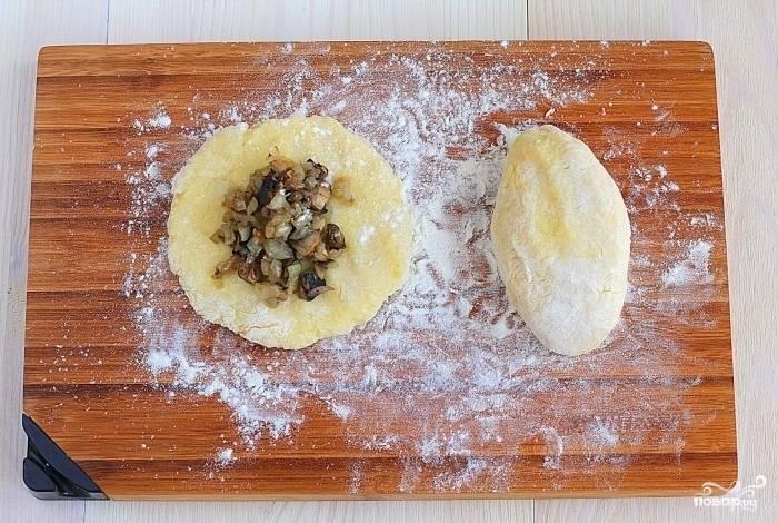 3.Полученное тесто разделите на 12 равных частей. Раскатайте их в лепешки, положите в центр каждой около 2 ч. л. грибной начинки. Сформуйте пирожки.