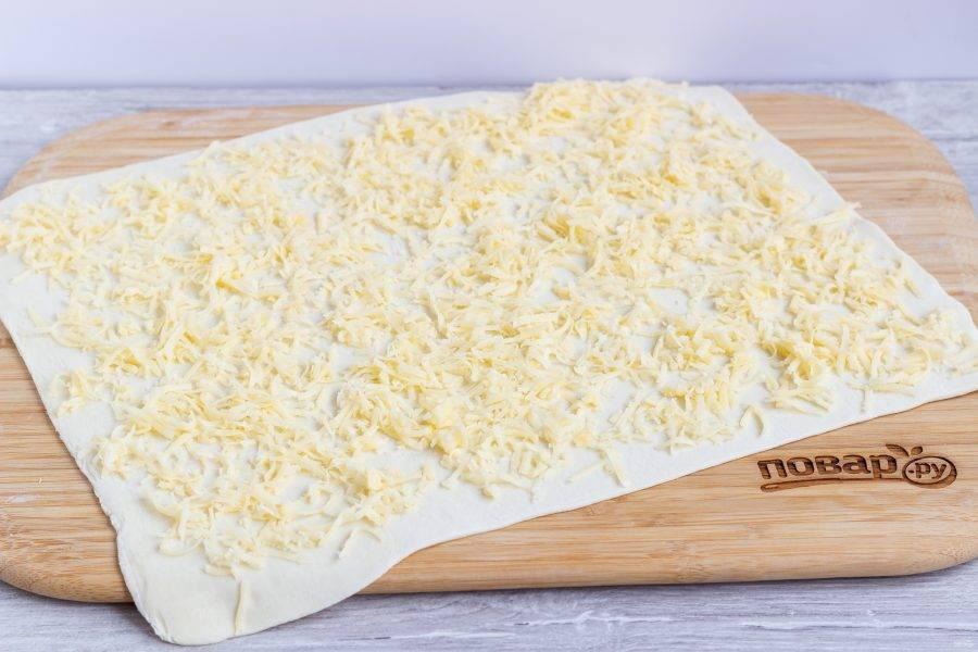Сыр натрите на мелкой терке, разделите пополам. Выложите половину сыра на раскатанный пласт.