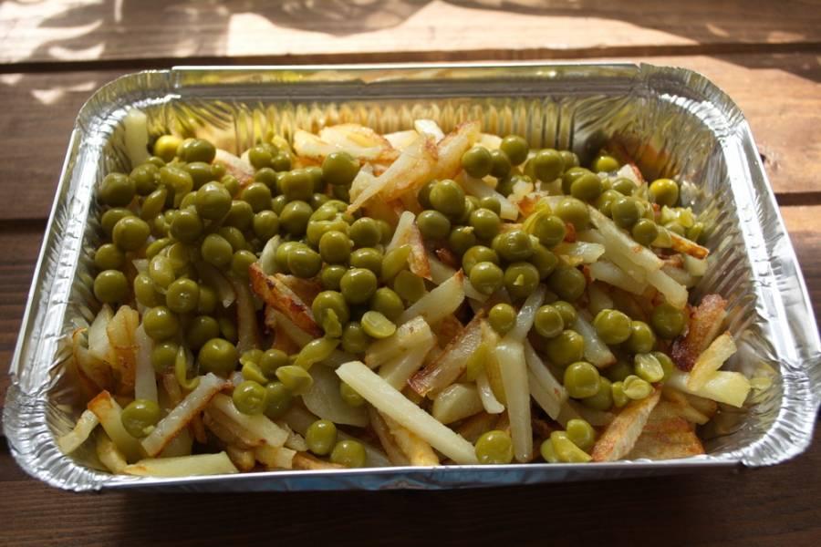 На слой картофеля выложите консервированный горошек.