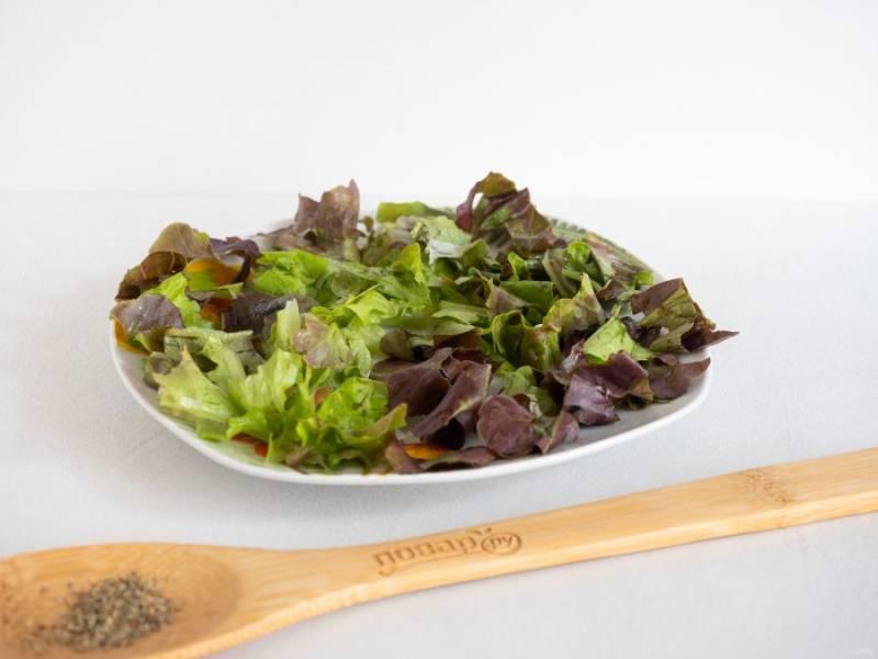 Салат нарвите руками и выложите на плоское блюдо.