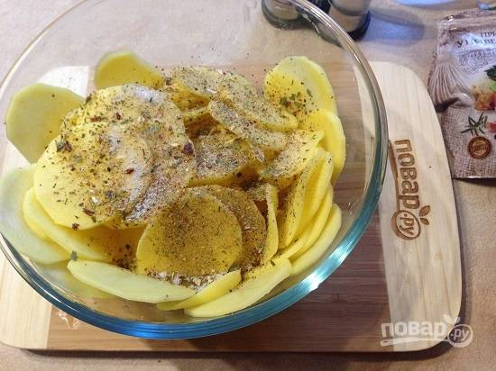 3. Добавляем к картофелю соль, приправу и молотый черный перец. Перемешаем очень тщательно.