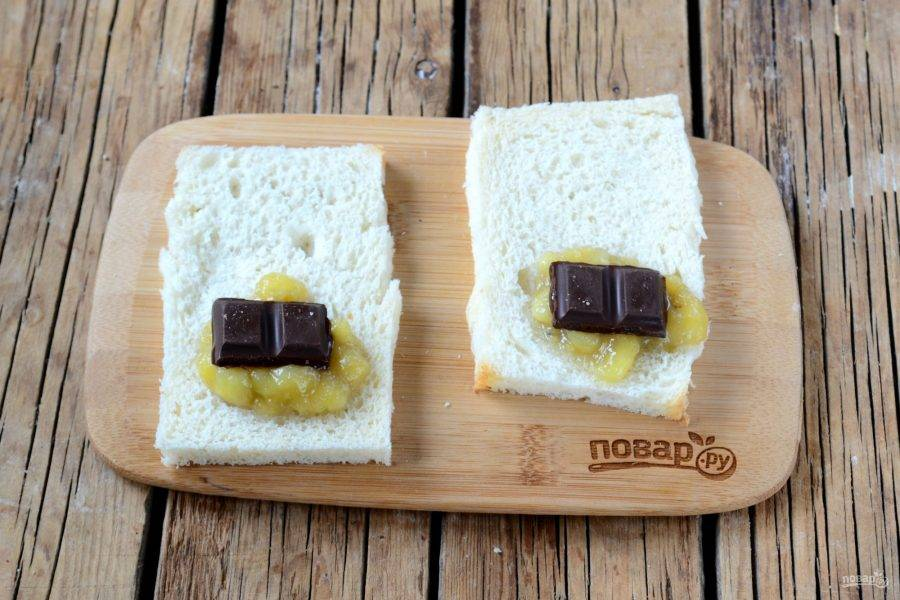 Края каждого ломтика хлеба обрежьте, чтобы остался только мякиш. Затем каждый ломтик раскатайте скалкой, чтобы удлинить хлеб и сделать его тоньше. На каждый ломтик положите примерно 1 ст. ложку без горки банановой массы и кубик шоколада.