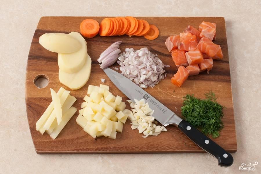 Затем мелкими кубиками нарезаем лук, мелко рубим чеснок и укроп. Филе рыбки нарезаем кубиками со стороной 1,5 см, картофель режем средними кубиками, а морковь нарезаем кружочками.