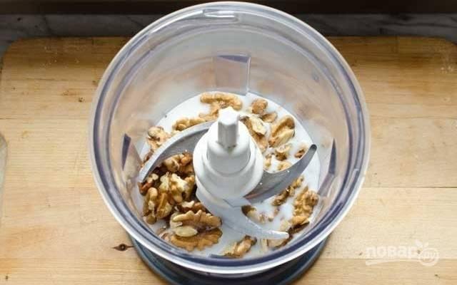 2.В чашу блендера положите крупно нарезанные ядра грецких орехов, влейте ¾ стакана молока и измельчите до однородной массы.