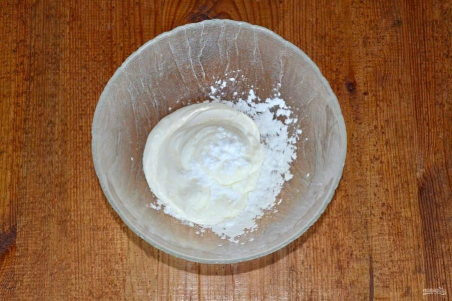 Для начала приготовьте крем. Для этого сметану соедините с сахарной пудрой и взбейте до пышности.