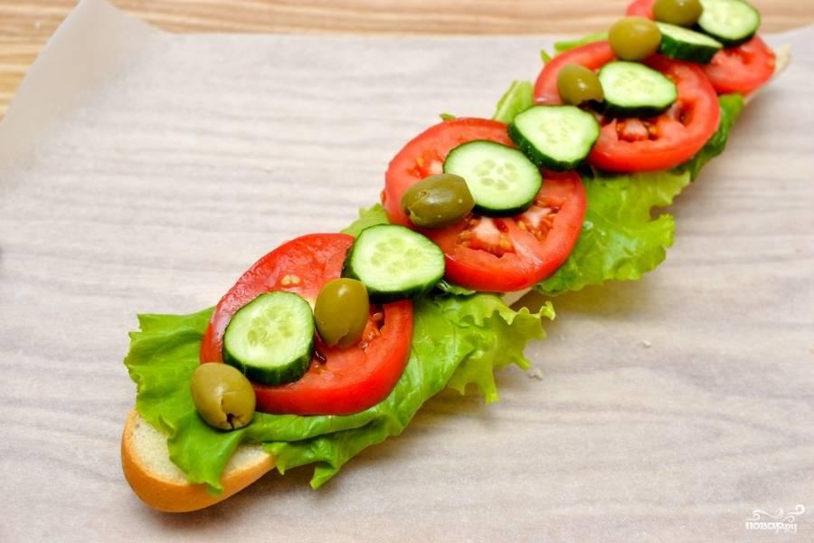 Пока верхушка запекается, на нижнюю часть багета выложите сначала листья салата, затем огурцы и помидоры (нарезанные кружочками) и оливки.