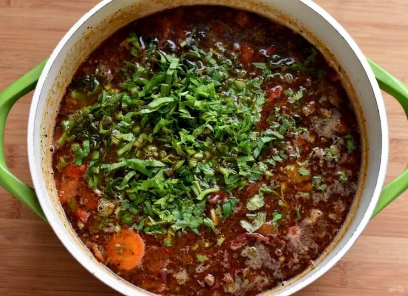Дайте прогреться и выложите содержимое сковороды в суп. Добавьте маслины, разрезанные пополам. Доведите до кипения, проварите пару минут. Опустите в суп нарубленную зелень и отключите нагрев.