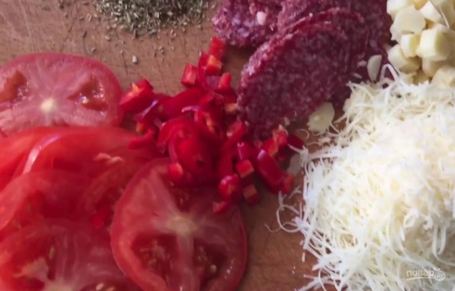 2. Подготовьте начинку. Нарежьте пластинками помидор и салями, кружочками сыр сулугуни и перец чили, натрите на мелкой терке твердый сыр.