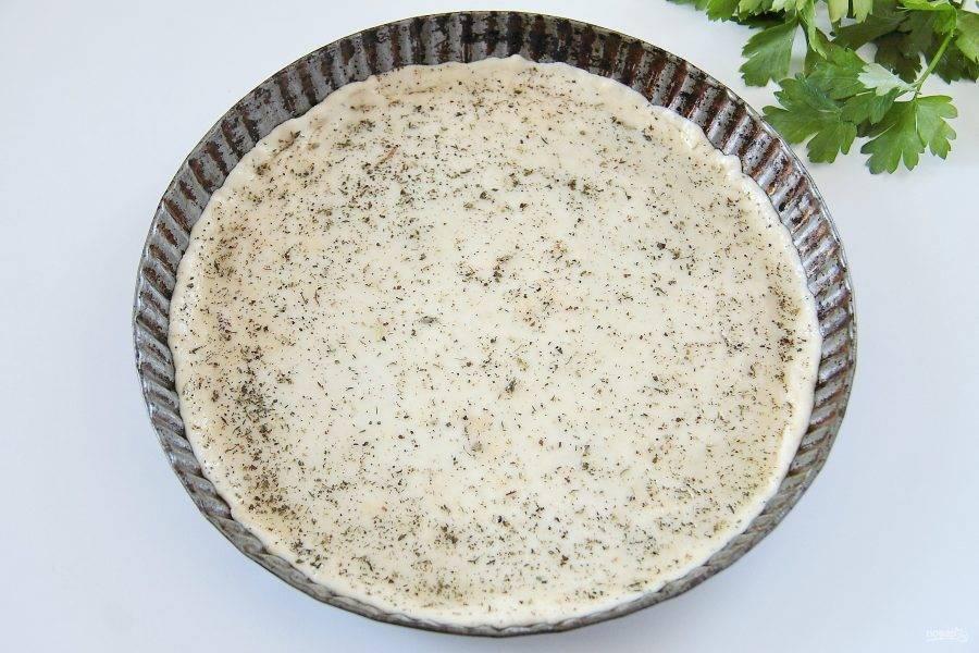 7. На слегка покрытой мукой поверхности раскатайте тонко тесто до желаемого размера и аккуратно перенесите в форму, предварительно смазав ее маслом. Руками сформируйте небольшие бортики. Смажьте поверхность оставшимся оливковым маслом, смешанным с прованскими травами.