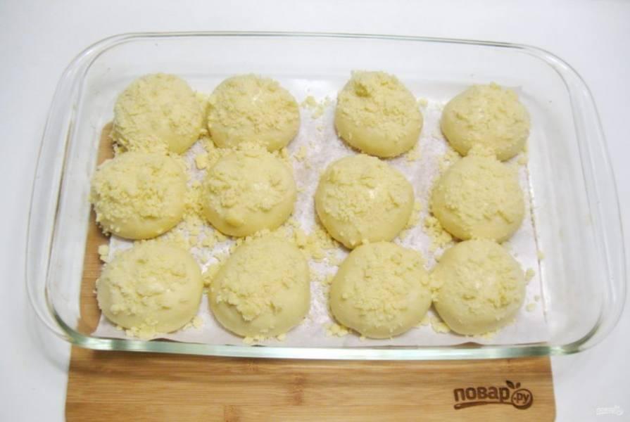Из сливочного масла, сахара и муки приготовьте штрейзель. Для этого смешайте эти ингредиенты до состояния крошки. Посыпьте штрейзелем булочки. Дайте им постоять в тепле 25-30 минут.