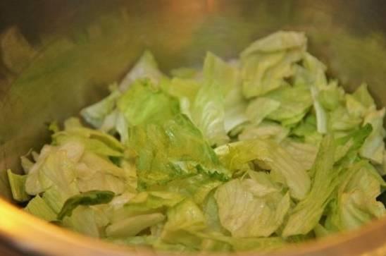Листья салата промываем, сушим и рвем руками на кусочки. Складываем в салатницу.