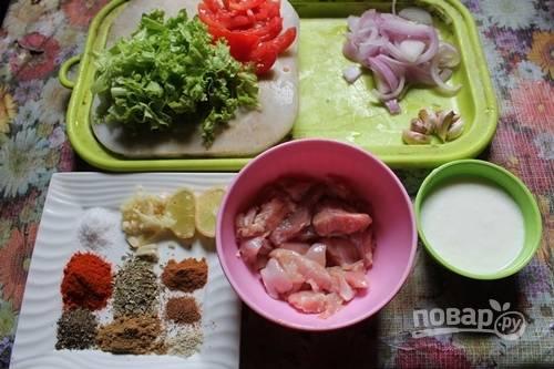 1.Подготовьте все ингредиенты: нарежьте кусочками куриное мясо. Нарежьте тонким полукольцами лук, кусочками томаты, крупно нарежьте листья салата.