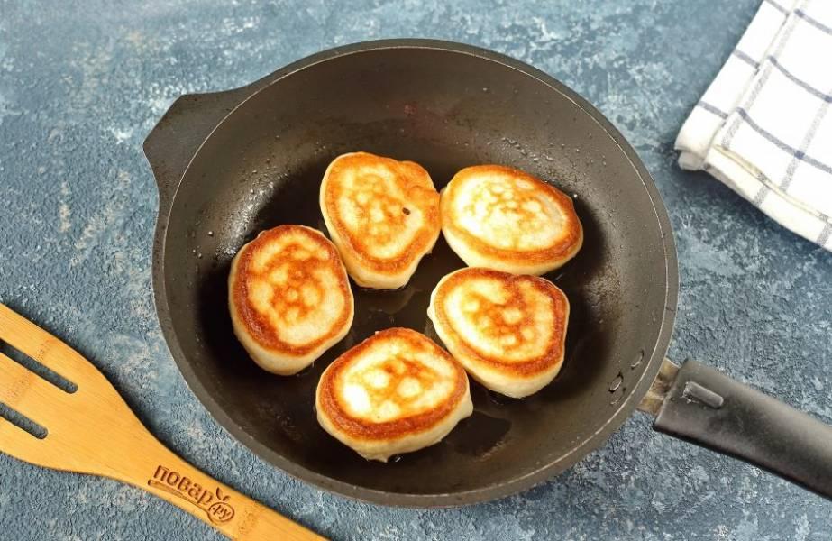 В сковороду налейте масло и подогрейте его. Для оладий нужно ровно столько, чтобы масло полностью покрывало дно. Зачерпываем одну полную столовую ложку теста и с помощью второй столовой ложки помогаем тесту спуститься в масло. Таким образом выкладываем столько оладий, сколько помещается в сковороде. Готовим на умеренном огне, пока у нижней стороны не образуется румяная корочка, а по бокам не появятся заметные пузыри. Затем аккуратно переворачиваем и готовим оладьи до зарумянивания второй стороны.