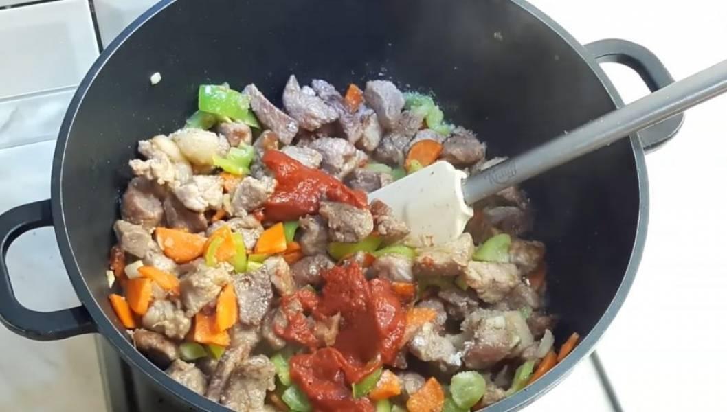 3. Добавьте морковь и обжарьте ее в течение 3 минут. Далее добавьте лук и жарьте 2 минуты. Затем добавьте сладкий перец и обжарьте все до готовности. Посолите, добавьте томатную пасту, лавровый лист, кардамон, острый перец и паприку.