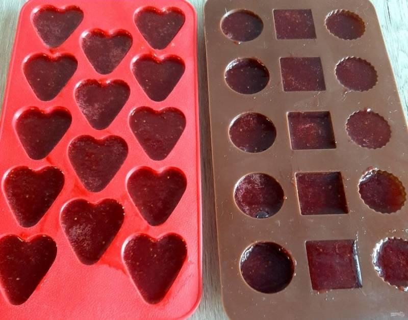 Разлейте получившуюся клубничную массу в формочки для приготовления льда или конфет. Конфеты начинают застывать даже при комнатной температуре, можно убрать в холодильник.