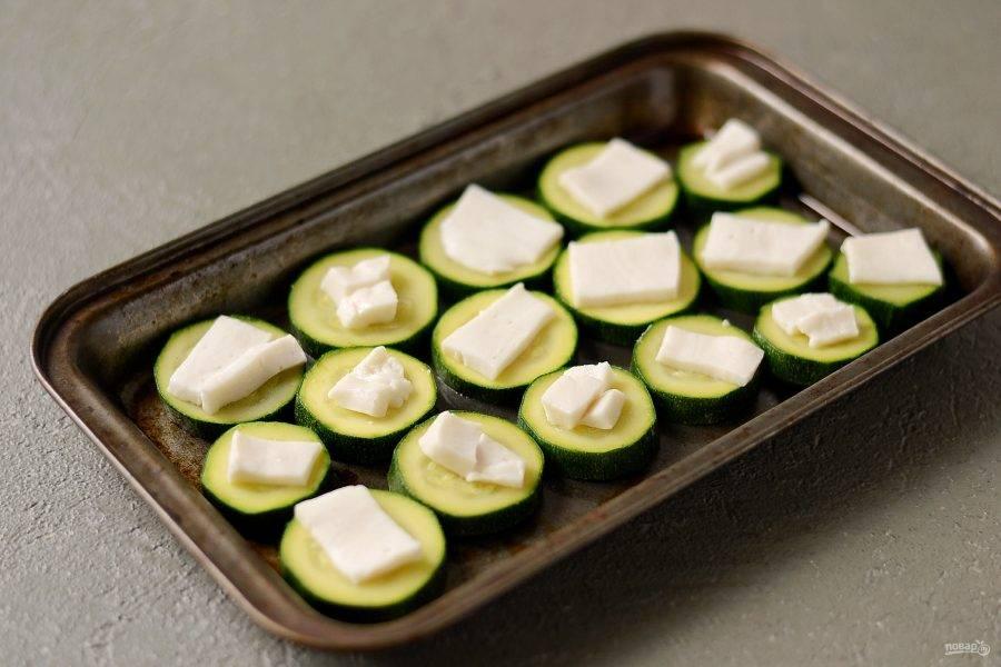 Переложите кабачки в форму для запекания. Нарежьте сыр пластинами и выложите на кружочки кабачков.