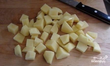 Чистим картофель и нарезаем небольшими кубиками. Отправляем картофель в кастрюлю с водой - примерно 2 литра и ставим на огонь.