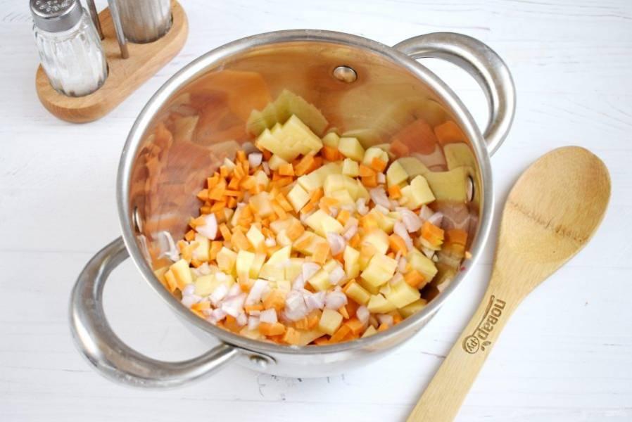 Все овощи, кроме капусты, нарежьте мелкими кубиками. В кастрюле с двойным дном или сотейнике разогрейте оливковое масло. Картофель, морковь, лук посолите и добавьте сушеный чеснок, кориандр. Обжарьте овощи  в течение 2 минут, помешивая. Если хотите получить более диетический вариант супа, то шаг с обжариванием пропустите. Залейте овощи водой, доведите до кипения. Варите на медленном огне в течение 5 минут.