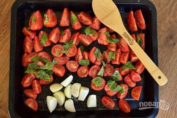 Помидоры разрежьте на средние ломтики, лук — помельче. Выкладывайте овощи на противень.  Сверху — листья базилика, порванные руками. Посыпьте солью, перцем и чесночным порошком, полейте оливковым маслом. Поставьте в разогретую до 200 °C духовку и запекайте в течение 40 минут. Выньте противень из духовки.