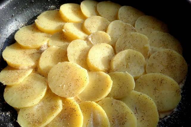 На дно вливаем немного теста и выкладываем слой картофеля.