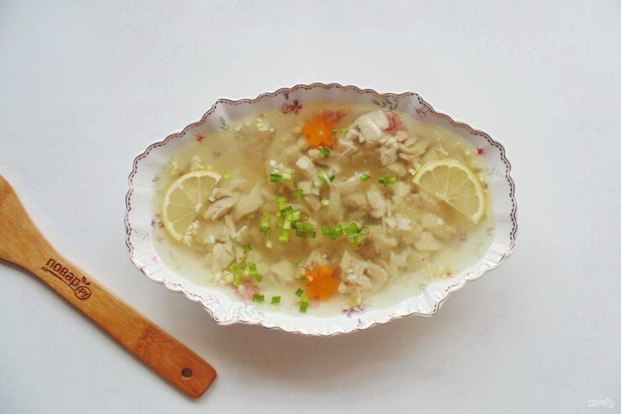 Залейте мясо куриным бульоном. Выложите в тарелки ломтики лимона и украсьте холодец по вкусу. Отправьте в холод до полного застывания.