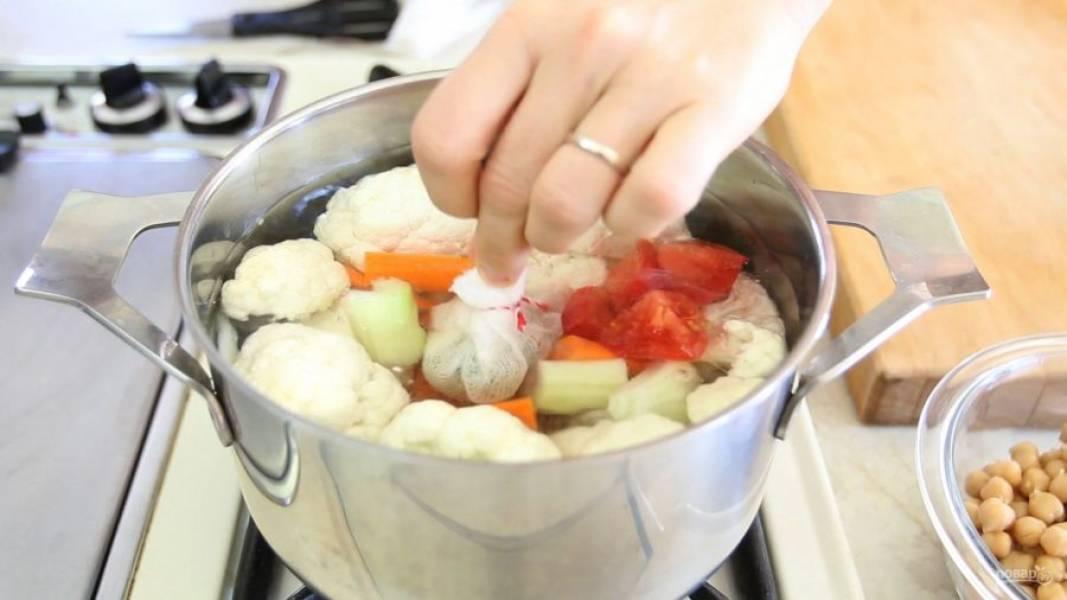 3. Овощи поместите в 3-3,5 литра воды в большую кастрюлю. Включите средний огонь. Выложите марлю с травами в воду.