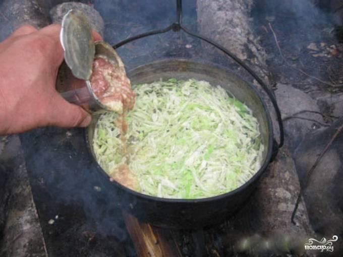 2. Тушенку добавьте в воду к капусте. Если в тушенке есть крупные куски мяса, предварительно помните их вилкой.