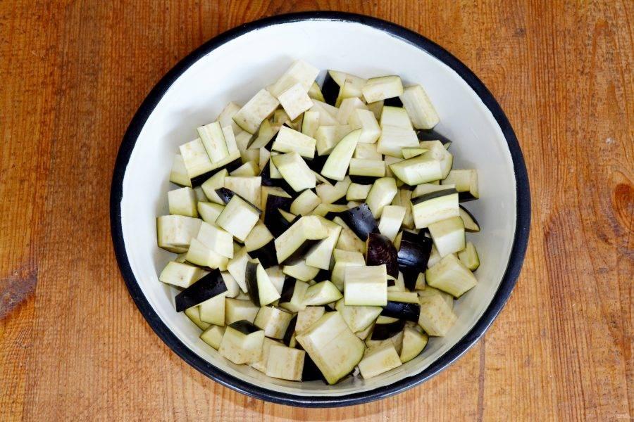 Нарежьте баклажаны кубиками, подсолите и оставьте на 35-40 минут. После тщательно промойте под проточной водой. Это избавит баклажаны от горечи.