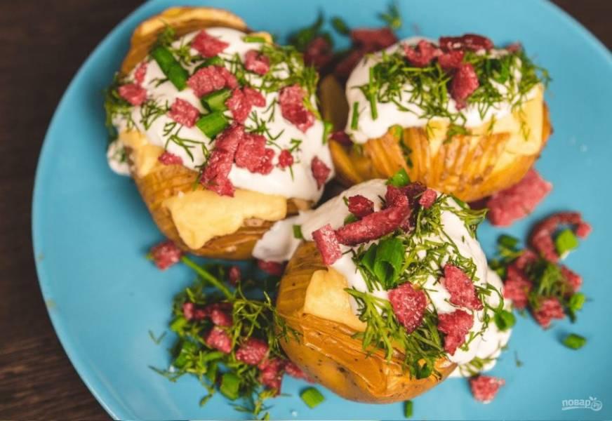 4. Затем снова поместите картофель в духовку на несколько минут, чтобы сыр расплавился. После этого украсьте блюдо сметаной, мелко нарезанной зеленью и поджаренной колбасой. Приятного аппетита!